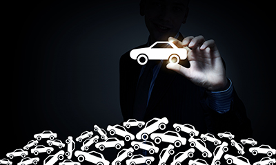 Businessman on dark background taking with fingers car icon